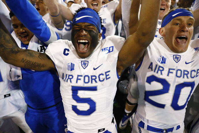 Air Force quarterback Donald Hammond III, left, and wide receiver Benjamin Waters lead teammates in a celebration after singing the school song after the second half of an NCAA college football game against Utah State Saturday, Oct. 26, 2019, at Air Force Academy, Colo. Air Force won 31-7. (AP Photo/David Zalubowski)
