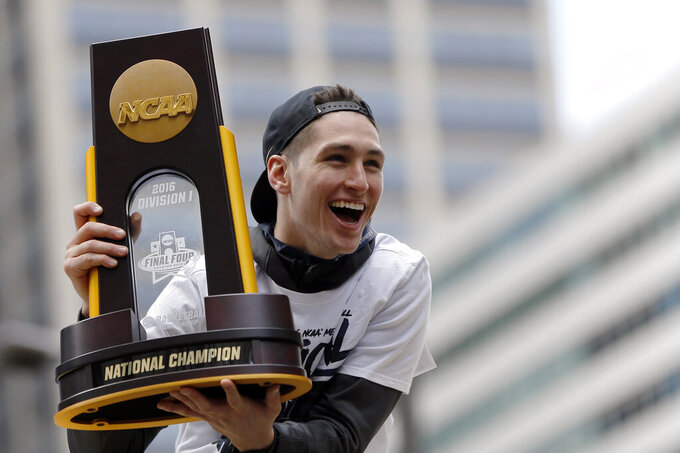 FILE - In this Friday, April 8, 2016, file photo, Villanova's Ryan Arcidiacono holds the trophy during a parade celebrating their NCAA college men's basketball championship, in Philadelphia. The NCAA and networks across the sports dial have infused fans with a hoops fix by rebroadcasting epic NCAA Tournament games. Coaches and players involved in those games are adding insight and a dash of humor by live tweeting during the replay. (AP Photo/Matt Rourke, File)