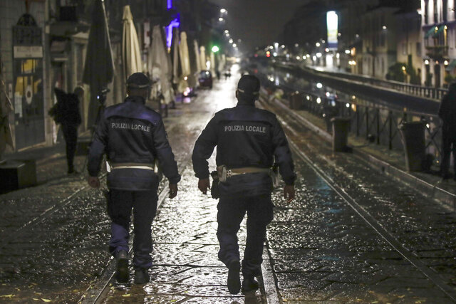 Two city police officers patrol the Navigli area, a popular evening spot of restaurants and pubs bordering canals in Milan, Italy, Thursday, Oct. 22, 2020. Authorities in regions including Italy's three largest cities have imposed curfews in a bid to slow the spread of COVID-19, as many of the cases in Lombardy's surging outbreak have occurred in Milan. On Thursday, an overnight curfew takes effect in the city, known for its lively night-time bar scene, and the rest of the region, as authorities try to slow the spread of the contagion. (AP Photo/Luca Bruno)