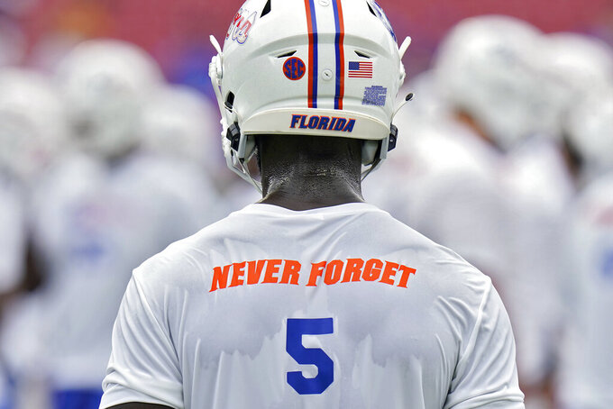"""Florida cornerback Kaiir Elam wears a """"never forget"""" t-shirt, in honor of the 20th anniversary of the Sept. 11, 2001 terrorist attacks, before an NCAA college football game against South Florida Saturday, Sept. 11, 2021, in Tampa, Fla. (AP Photo/Chris O'Meara)"""