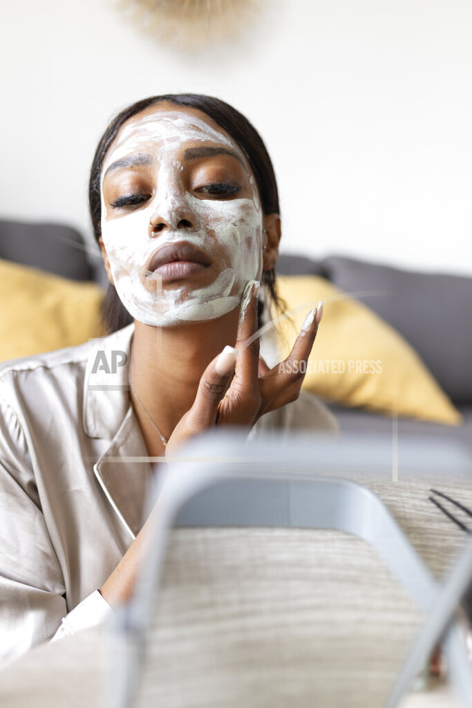 Young woman taking skin care mask at home