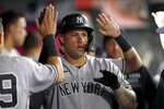 New York Yankees' Gary Sanchez is congratulated in the dugout after hitting a solo home run during the fifth inning of the team's baseball game against the Los Angeles Angels in Anaheim, Calif., Tuesday, Aug. 31, 2021. (AP Photo/Alex Gallardo)