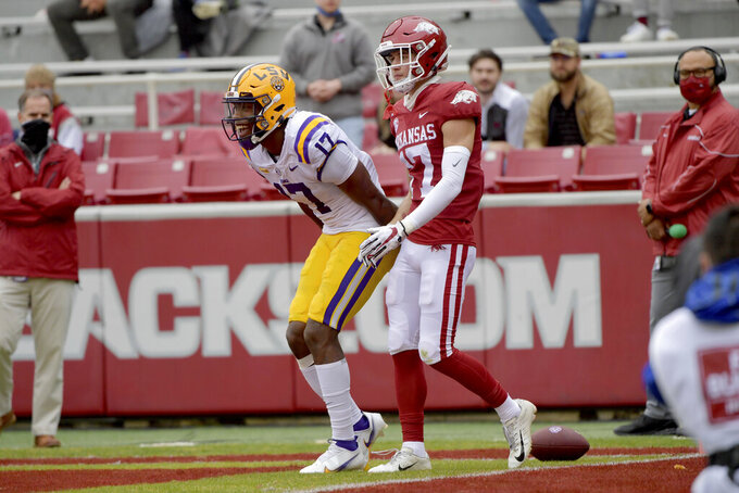 LSU receiver Racey McMath (17) celebrates after a touchdown catch in front of Arkansas defender Hudson Clark (17) during the first half of an NCAA college football game Saturday, Nov. 21, 2020, in Fayetteville, Ark. (AP Photo/Michael Woods)