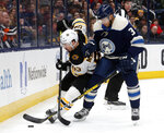 Boston Bruins forward Brad Marchand, left, tries to control the puck next to Columbus Blue Jackets defenseman Seth Jones during the first period  of an NHL hockey game in Columbus, Ohio, Tuesday, Jan. 14, 2020. (AP Photo/Paul Vernon)
