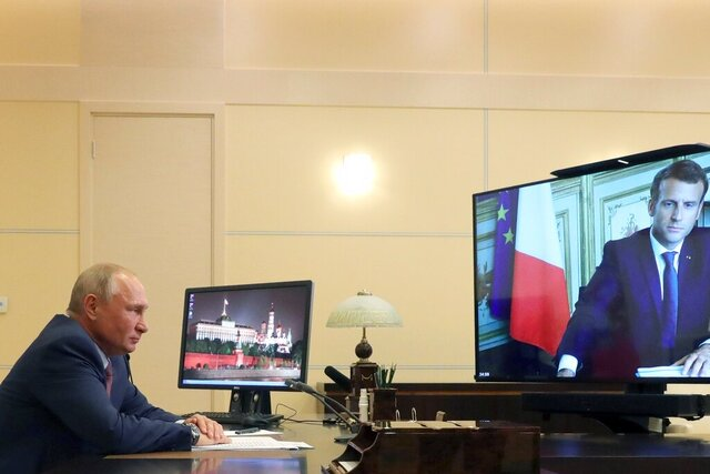 Russian President Vladimir Putin listens to French President Emmanuel Macron during a via video conference at the Novo-Ogaryovo residence outside Moscow, Russia, Friday, June 26, 2020. (Mikhail Klimentyev, Sputnik, Kremlin Pool Photo via AP)