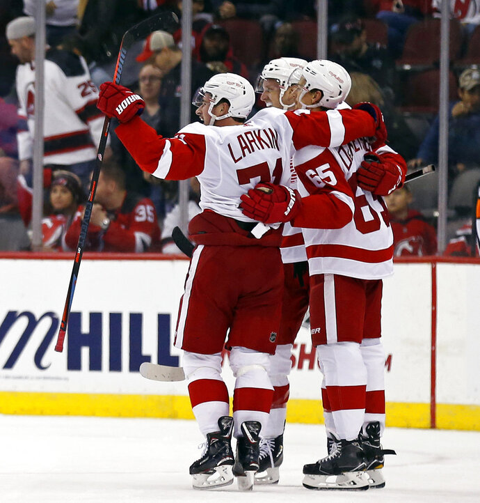 Detroit Red Wings center Dylan Larkin (71) celebrates with teammates after scoring the game-winning goal against the New Jersey Devils during overtime of an NHL hockey game Saturday, Nov. 17, 2018, in Newark, N.J. The Red Wings won in overtime 3-2. (AP Photo/Adam Hunger)