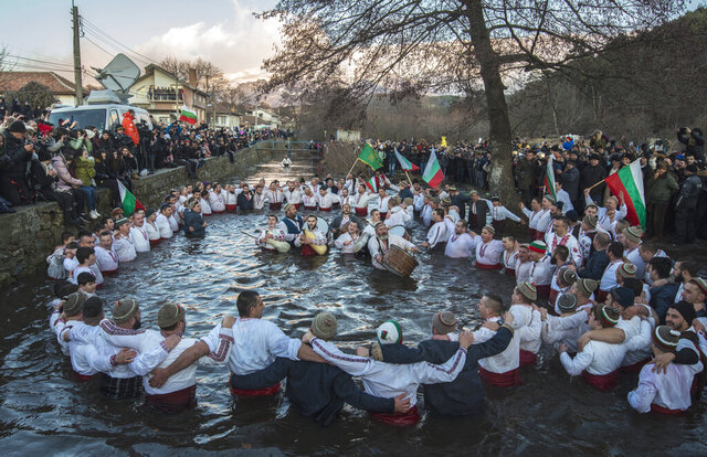 Bulgarians sing, play bagpipes and chain dance in the icy waters of the Tundzha river during Epiphany, in Kalofer, Bulgaria, Monday, Jan. 6, 2020. Thousands of Orthodox Christian worshippers plunged into the icy waters of rivers and lakes across Bulgaria on Monday to retrieve crucifixes tossed by priests in ceremonies commemorating the baptism of Jesus Christ. In the mountain city of Kalofer, in central Bulgaria, dozens of men dressed in white embroidered shirts waded into the frigid Tundzha River waving national flags and singing folk songs. (AP Photo)
