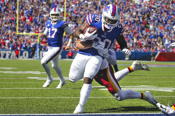Buffalo Bills running back Zack Moss (20) runs past Washington Football Team's Cole Holcomb for a touchdown as Bills' quarterback Josh Allen (17) watches during the first half of an NFL football game Sunday, Sept. 26, 2021, in Orchard Park, N.Y. (AP Photo/Jeffrey T. Barnes)