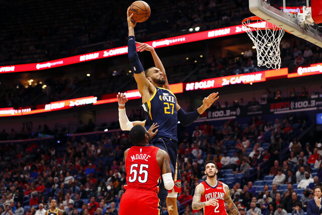 Utah Jazz center Rudy Gobert (27) drives to the basket in front of New Orleans Pelicans guard E'Twaun Moore (55) in the second half of an NBA basketball game in New Orleans, Monday, Jan. 6, 2020. (AP Photo/Tyler Kaufman)