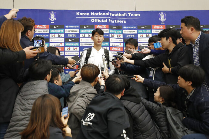 South Korean national soccer team player Son Heung-min answers reporter's question upon his arrival after the soccer match against North Korea, at Incheon International Airport in Incheon, South Korea, Thursday, Oct. 17, 2019. North Korea held South Korea to a 0-0 draw Tuesday in a World Cup qualifying soccer match played in an empty stadium in Pyongyang, but specific details of the game weren't immediately available. South Korean soccer officials were unable to watch a telecast of the historic game at Kim Il Sung Stadium and South Korean spectators and media were denied entry. (AP Photo/Lee Jin-man)