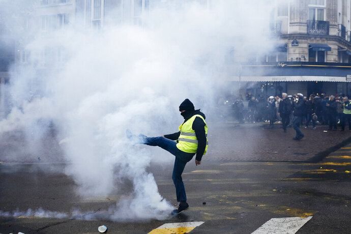 A protestor kicks away a tear gas canister during a yellow vest demonstration marking the first anniversary in Paris, Saturday, Nov. 16, 2019. Paris police fired tear gas to push back yellow vest protesters trying to revive their movement on the first anniversary of the sometimes violent uprising against President Emmanuel Macron and government economic policies (AP Photo/Kamil Zihnioglu)