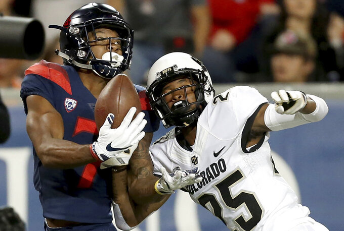 Arizona wide receiver Devaughn Cooper (7) makes a one-handed catch despite being wrapped up by Colorado cornerback Mekhi Blackmon (25) during the second quarter of an NCAA college football game Friday, Nov. 2, 2018, in Tucson, Ariz. (Kelly Presnell/Arizona Daily Star via AP)