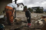 Michiko Yoshimura, left, bows to her neighbor as they comfort each other while cleaning up her home damaged by Typhoon Hagibis Tuesday, Oct. 15, 2019, in Nagano, Japan. More victims and more damage have been found in typhoon-hit areas of central and northern Japan, where rescue crews are searching for people still missing. (AP Photo/Jae C. Hong)