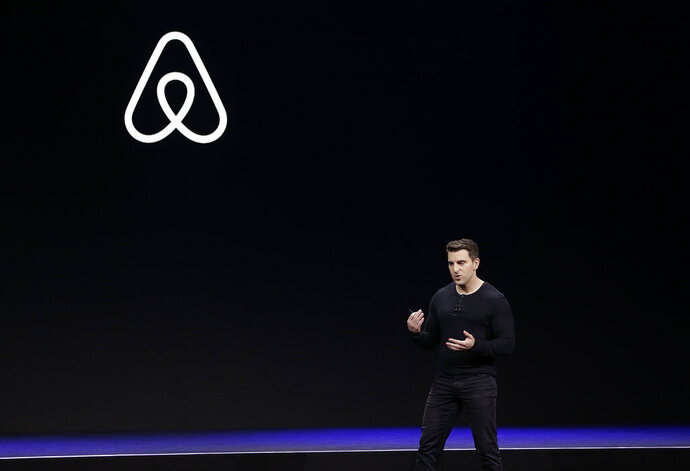 FILE - In this Feb. 22, 2018, file photo Airbnb co-founder and CEO Brian Chesky speaks during an event in San Francisco.   Just as the coronavirus outbreak has boxed in society, it's also squeezed high-flying tech companies reliant on people's freedom to move around and get together. Airbnb, which just weeks ago was planning for a bombshell initial public offering, is reportedly shedding millions of dollars and facing harsh blowback from hosts who relied on its platform for income.  (AP Photo/Eric Risberg, File)
