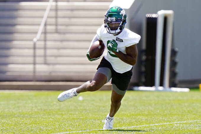 New York Jets wide receiver Elijah Moore carries the ball after catching a pass during an NFL football practice, Thursday, May 27, 2021, in Florham Park, N.J. (AP Photo/Kathy Willens)