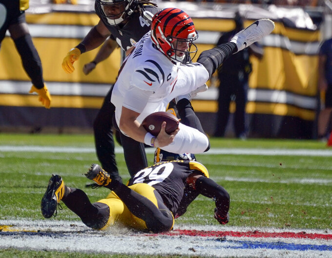 Cincinnati Bengals quarterback Joe Burrow (9) tumbles over Pittsburgh Steelers free safety Minkah Fitzpatrick (39) after scrambling for a first down during the first half an NFL football game, Sunday, Sept. 26, 2021, in Pittsburgh. (AP Photo/Gene J. Puskar)
