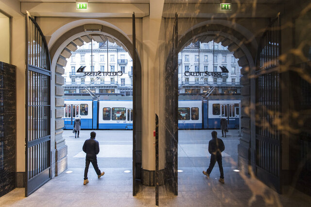 """FILE- In this Feb. 14, 2018, file photo, people walk in the front of the Credit Suisse bank at the tram stop Paradeplatz in the square's centre in Zurich, Switzerland. Switzerland's financial market oversight body said Wednesday, Sept. 2, 2020 that it has opened """"enforcement proceedings"""" against Credit Suisse in the wake of a spying scandal that has marred the image of the elite bank. (Ennio Leanza/Keystone via AP, File)"""
