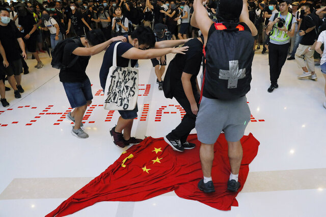 In this Sunday, Sept. 22, 2019, photo, protesters walk on a Chinese national flag during a protest at a mall in Hong Kong. China's decision to impose a national security law on Hong Kong is raising questions about the future of the semi-autonomous Chinese territory. The move bypasses Hong Kong's government _ which has not been able to enact such a law despite a requirement that it does _ and could allow the stationing of Chinese security officers in the city. A look at what it means and why people are concerned. (AP Photo/Kin Cheung)