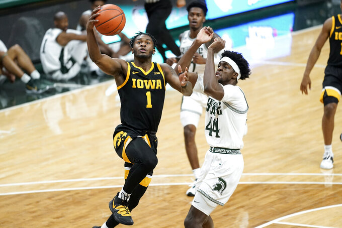 Iowa guard Joe Toussaint (1) drives on Michigan State forward Gabe Brown (44) in the first half of an NCAA college basketball game in East Lansing, Mich., Saturday, Feb. 13, 2021. (AP Photo/Paul Sancya)