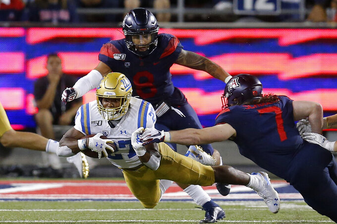 FILE - In this Sept. 28, 2019, file photo, UCLA running back Joshua Kelley (27) dives for a first down in between Arizona linebackers Anthony Pandy and Colin Schooler (7) in the second half during an NCAA college football game, in Tucson, Ariz. Kelley was selected to The Associated Press All-Pac 12 Conference team, Thursday, Dec. 12, 2019.  (AP Photo/Rick Scuteri, File)