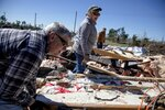 Cindy Sanford, center, sifts through the debris with help from her brother, Tim Lancaster, left, and stepfather, Michael Boutwell, while retrieving personal items after a tornado destroyed her home in Beauregard, Ala., Tuesday, March 5, 2019. (AP Photo/David Goldman)