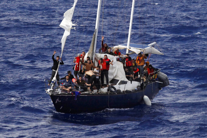 Migrants wave for help as they wait for the Italian coast guard to rescue them, on international waters in the Mediterranean Sea, Sunday, Sept. 12, 2021. (AP Photo/Samy Magdy)