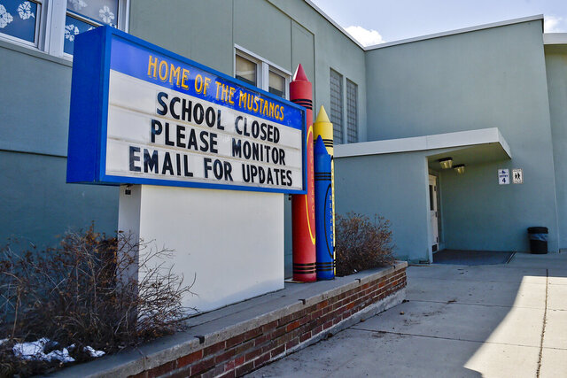 FILE - This Thursday, April 16, 2020 file photo shows a sign announcing an elementary school in Helena, Mont., is closed. When the coronavirus pandemic took hold across the United States in mid-March, forcing schools to close and many children to be locked down in households buffeted by job losses and other forms of stress, many child-welfare experts warned of a likely surge of child abuse. Fifteen weeks later, the worries persist — yet some experts on the front lines, including pediatricians who helped sound the alarm, say they've seen no evidence yet that a marked increase has taken place. (Thom Bridge/Independent Record via AP)