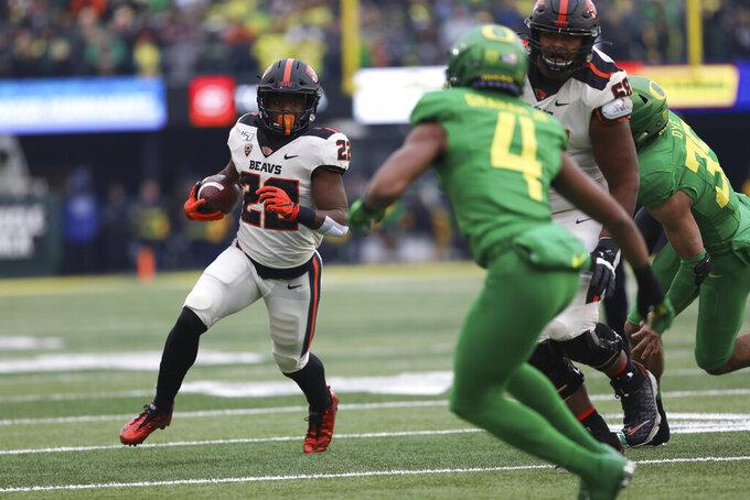 Oregon State running back Jermar Jefferson (22) tries to avoid Oregon cornerback Thomas Graham Jr. (4) during the first half of an NCAA college football game in Eugene, Ore., Saturday, Nov. 30, 2019. (AP Photo/Amanda Loman)