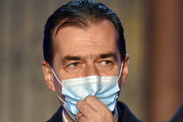 FILE - In this Sunday, Dec. 6, 2020 file photo, Romanian Prime Minister Ludovic Orban and head of the ruling National Liberal party adjusts his mask after exit polls in the country's parliamentary elections were announced, in Bucharest, Romania. Romania's center-right prime minister Ludovic Orban resigned Monday Dec. 7, 2020, after a general election in which voters delivered nominal victory to the left-leaning, populist opposition party. (AP Photo/Andreea Alexandru, File)