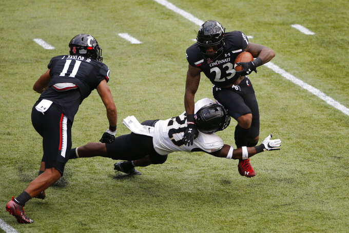 Cincinnati running back Gerrid Doaks, right, tries to escape the grasp of Army's Marquel Broughton during the first half of an NCAA college football game Saturday, Sept. 26, 2020, in Cincinnati, Ohio. (AP Photo/Jay LaPrete)