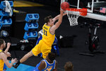 Michigan guard Franz Wagner (21) drives to the basket over UCLA forward Kenneth Nwuba (14) during the first half of an Elite 8 game in the NCAA men's college basketball tournament at Lucas Oil Stadium, Tuesday, March 30, 2021, in Indianapolis. (AP Photo/Michael Conroy)