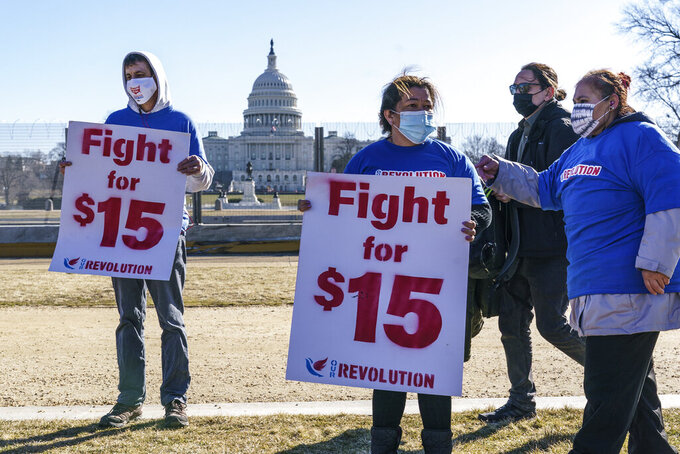 Activists appeal for a $15 minimum wage near the Capitol in Washington, Thursday, Feb. 25, 2021. The $1.9 trillion COVID-19 relief bill being prepped in Congress includes a provision that over five years would hike the federal minimum wage to $15 an hour. (AP Photo/J. Scott Applewhite)