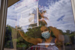 A clothing store worker poses next to a sign encouraging the use of a masks during the COVID-19 pandemic at the entrance to the store in Managua, Nicaragua, Thursday, Sept. 9, 2021. (AP Photo/Miguel Andres)