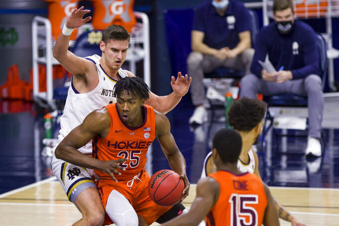 Virginia Tech's Justyn Mutts (25) gets pressure under the basket from Notre Dame's Nate Laszewski, left, during the first half of an NCAA college basketball game Wednesday, Jan. 27, 2021, in South Bend, Ind. (AP Photo/Robert Franklin)