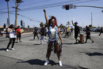 A protester raises her fist during a march in honor of Andres Guardado on Sunday, June 21, 2020, in Compton, Calif. Guardado was shot Thursday after Los Angeles County sheriff's deputies spotted him with a gun in front of a business near Gardena. (AP Photo/Marcio Jose Sanchez)