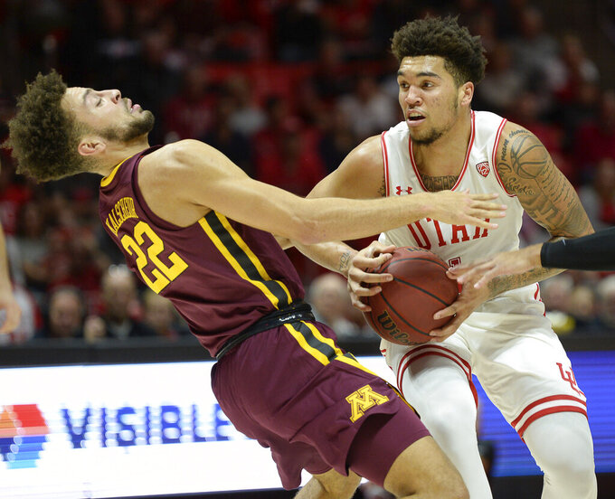 Minnesota guard Gabe Kalscheur (22) gets knocked over by Utah forward Timmy Allen during an NCAA college basketball game Friday, Nov. 15, 2019, in Salt Lake City. (Francisco Kjolseth/The Salt Lake Tribune via AP)