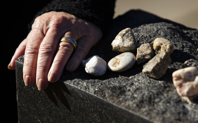 Dr. Lilly Filler rests her hand on a memorial for victims of the Holocaust and Filler's family who survived the Holocaust at Beth Shalom Cemetery on Thursday, Dec. 10, 2020. She and her siblings placed the gravestone to honor all of their family members they never had the chance to meet because of their deaths in the Holocaust. (Joshua Boucher/The State via AP)