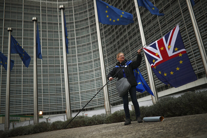 A woman holds a mix of Union Flag and EU flag during an anti-Brexit protest outside the European Commission headquarters in Brussels, Wednesday, Oct. 9, 2019. A small group of anti-Brexit campaigners has staged a protest at the European Commission's headquarters in Brussels asking for a rejection of British Prime minister Boris Johnson's proposals for his country's planned exit from the bloc. (AP Photo/Francisco Seco)
