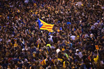 A pro-independence Estelada flag is waved among protestors during a demonstration in Barcelona, Spain, Wednesday, Oct. 16, 2019. Spain's government said Wednesday it would do whatever it takes to stamp out violence in Catalonia, where clashes between regional independence supporters and police have injured more than 200 people in two days. (AP Photo/Bernat Armangue)