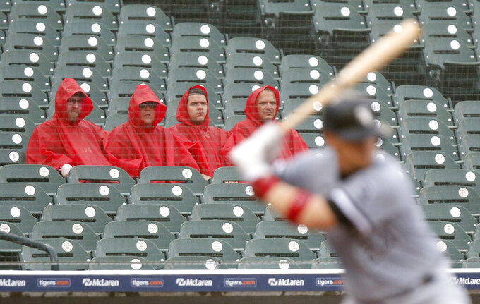 Fans watch Chicago White Sox's Yasmani Grandal bat as rain falls during the third inning of a baseball game against the Detroit Tigers on Tuesday, Sept. 21, 2021, in Detroit. (AP Photo/Duane Burleson)