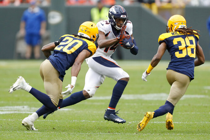 Denver Broncos wide receiver Courtland Sutton (14) runs with the ball as Green Bay Packers cornerbacks Kevin King (20) and Tramon Williams (38) defend during the second half of an NFL football game Sunday, Sept. 22, 2019, in Green Bay, Wis. (AP Photo/Matt Ludtke)