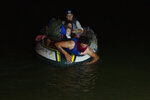 FILE - IN this March 30, 2021, file photo, a smuggler takes migrants, mostly from Central American countries, on a small inflatable raft towards U.S. soil in Roma, Texas. Migrant families will be held at hotels in the Phoenix area in response to a growing number of people crossing the U.S.-Mexico border, authorities said Friday, April 9, 2021 another step in the Biden administration's rush to set up temporary space for them (AP Photo/Dario Lopez-Mills, File)