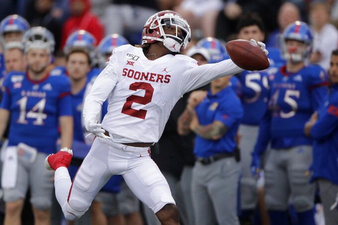 Oklahoma wide receiver CeeDee Lamb (2) reaches for but can't catch a long pass during the first half of an NCAA college football game against Kansas, Saturday, Oct. 5, 2019, in Lawrence, Kan. (AP Photo/Charlie Riedel)