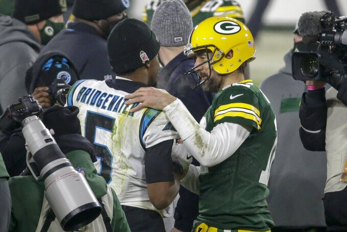Green Bay Packers' Aaron Rodgers talks to Teddy Bridgewater after an NFL football game Saturday, Dec. 19, 2020, in Green Bay, Wis. The Packers won 24-16. (AP Photo/Mike Roemer)