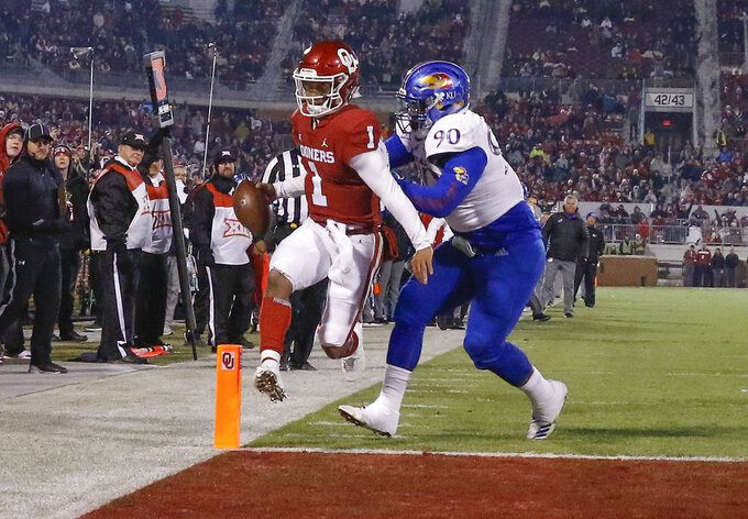 FILE - In this Nov. 17, 2018, file photo, Oklahoma quarterback Kyler Murray (1) runs in for a touchdown ahead of Kansas defensive tackle Jelani Brown (90) during the second half of an NCAA college football game, in Norman, Okla. Murray was named a Heisman Trophy finalist on Monday, Dec. 3, 2018. (AP Photo/Alonzo Adams, File)