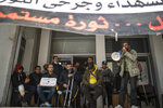 People who were injured during Tunisia's democratic uprising 10 years ago, stage a protest demanding official recognition, in Tunis, Tunisia, Tuesday, Jan. 12, 2021. Banner in Arabic read