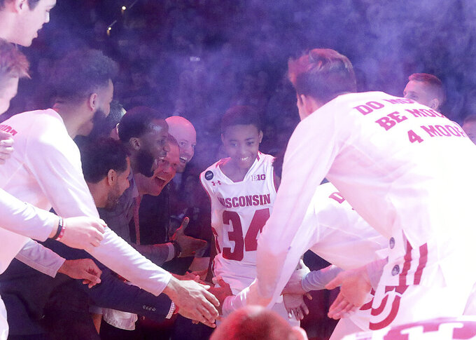 Jerrell Moore, son of Wisconsin Badgers assistant coach Howard Moore, takes the court as an honorary sixth man before the team's NCAA college basketball game against Eastern Illinois in Madison, Wis. Friday, Nov. 8, 2019. The two were in a May 25, 2019 vehicle crash that claimed the life of the coach's wife, Jennifer, and daughter, Jaidyn. The elder Moore has continued to face health challenges since the accident was unable to attend the game. (John Hart/Wisconsin State Journal via AP)