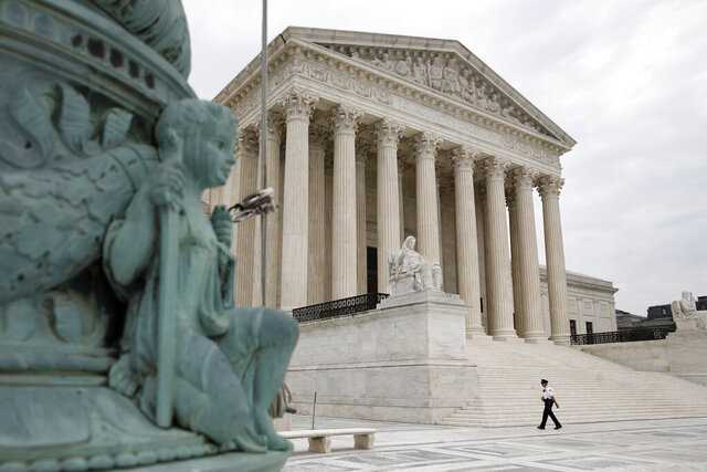 A police officer walks outside the Supreme Court on Capitol Hill in Washington, Monday, July 6, 2020. (AP Photo/Patrick Semansky)