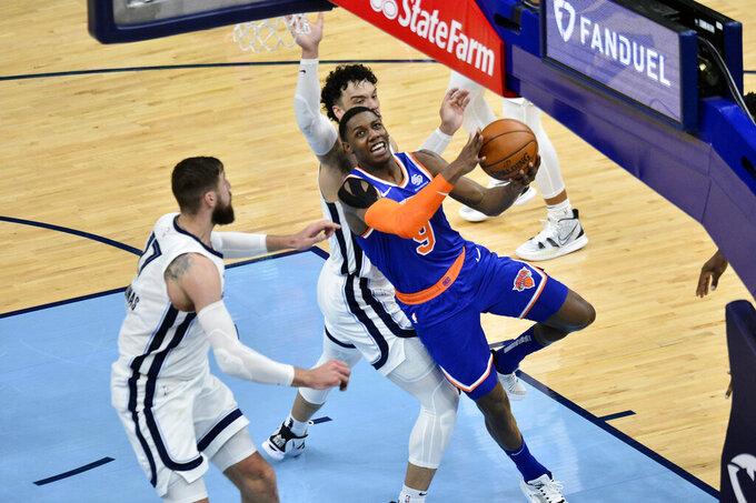 New York Knicks guard RJ Barrett (9) shoots ahead of Memphis Grizzlies center Jonas Valanciunas (17) and forward Dillon Brooks in the second half of an NBA basketball game Monday, May 3, 2021, in Memphis, Tenn. (AP Photo/Brandon Dill)