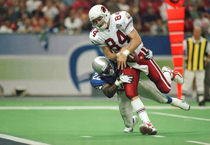 FILE - In this Sept. 13, 1998, file photo, Arizona Cardinals' Chris Gedney (84) takes in a pass while in the grasp of Seattle Seahawks' Fred Thomas (22) and goes for a touchdown in the fourth quarter of an NFL football game in Seattle. Gendey, an All-American tight end at Syracuse who played in the NFL for the Chicago Bears and Cardinals, has died, Syracuse University announced Friday, March 9, 2018.  He was 47.  (AP Photo/Jay Drowns, File)
